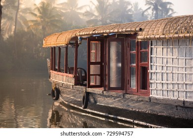 A traditional house boat is anchored on the shores of a fishing lake in Kerala's Backwaters.