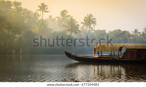 A traditional house boat is anchored on the shores of a fishing lake in Kerala's Backwaters, India.