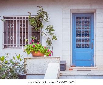 traditional house entrance light blue door and flowerpot, Athens Greece