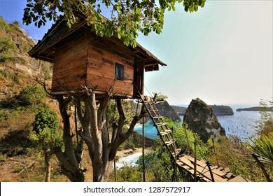 Traditional house on tree, couple look at Atun beach, Nusa Penida island. Popular travel destination on Bali holidays. Indonesia