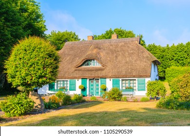 Traditional house with straw roof in and sunny blue sky near Ostseebad Sellin, Ruegen island, Baltic Sea, Germany