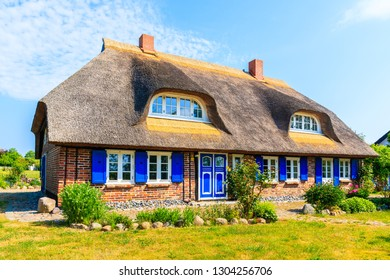 Traditional house with straw roof and sunny blue sky in Middelhagen village, Ruegen island, Baltic Sea, Germany