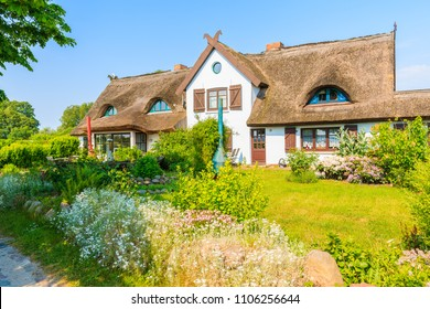 Traditional house with thatched roof and sunny blue sky in Gross Stresow village, Ruegen island, Baltic Sea, Germany