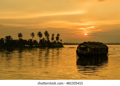A traditional houseboat moves past the setting sun on the Kerala Backwaters in India.