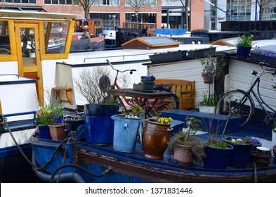 Traditional houseboats on a canal in Amsterdam, Netherlands, plant pots and a bike on the deck, park bench and table, spring, advertising for travel, lodging, sightseeing