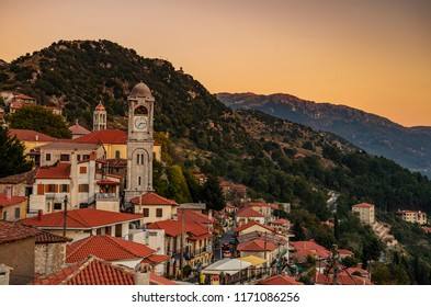 Traditional houses of Dimitsana village with the tall clock tower dominating against a cloudy sky. Arcadia Peloponnese, Greece, Europe.
