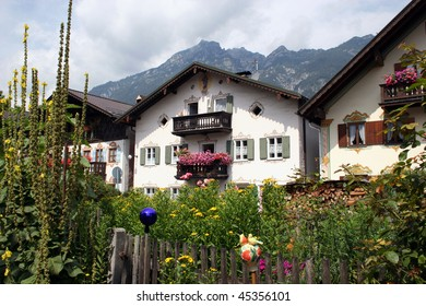 Traditional houses and garden with flowers in Garmisch-Partenkirchen, Bavaria (Germany), in the background the Ammergebirge mountains. Picture was made from the public area.