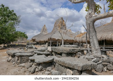 Traditional houses on stilts with thatched roofs with megalithic tombs in Prai Ijing village, Sumba island, East Nusa Tenggara, Indonesia