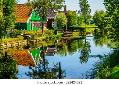 Traditional Houses reflecting in the Canal in the Historic Village of Zaanse Schans on the Zaan River in the Netherlands