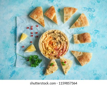 Traditional hummus and broken bread pellet on parchment.