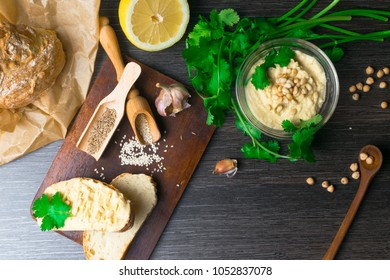 Traditional Hummus or houmous, appetizer made of mashed chickpeas with tahini, lemon, garlic, olive oil, parsley, cumin and cedar nuts on wooden table. Healthy lifestyle and eating right concept