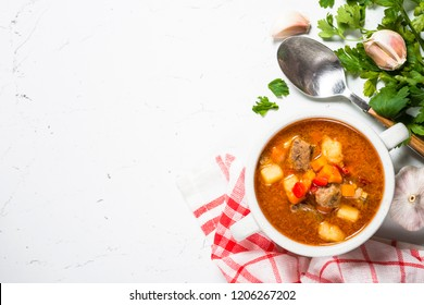 Traditional Hungarian goulash soup on white stone table. European cuisine. Top view with copy space.