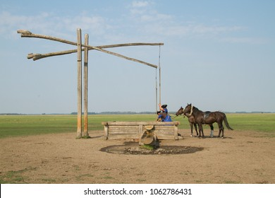 Traditional Hungarian horsemen getting water from well for horses in the Great Hungarian Plain in Hortobagy