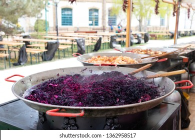 Traditional hungarian street food with purple cabbage cooking in a large pot. Seating area in the background, out of focus, no people.