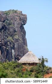A traditional hut below the dame de mali rock formation in fouta djalon mountains in Guinea