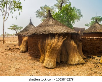 Traditional huts in an african village of Burkina Faso with some bundles of straw stored against their circular walls made of mud bricks.