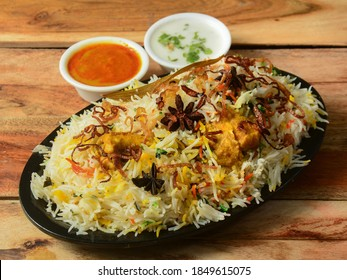 Traditional Hyderabadi Chicken dum Biryani made of Basmati rice cooked with masala spices, served with Onion raita and Salan, selective focus - Shutterstock ID 1849615075
