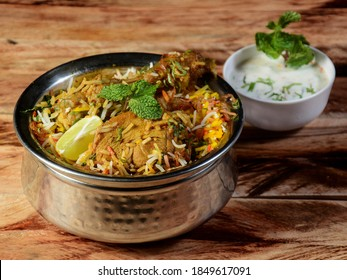 Traditional Hyderabadi Chicken dum Biryani made of Basmati rice cooked with masala spices, served with Onion raita, selective focus - Shutterstock ID 1849617091