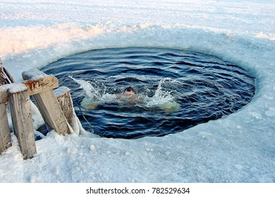 Traditional ice swimming in Orthodox church Holy Epiphany Day. Ice-hole for bathing (air temperature minus 37 degrees Celsius) on Epiphany day