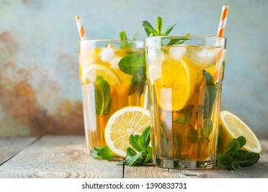 Traditional iced tea with lemon and ice in tall glasses on a wooden rustic table