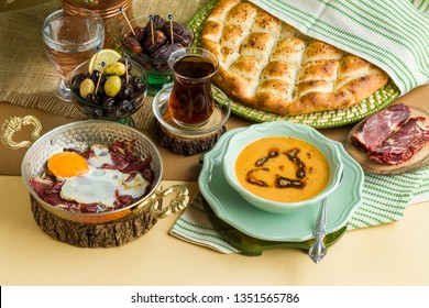 Traditional iftar begining meal with soup,dry age meat cooked egg,tea,ramadan fresh bread,water,olives and dry date fruits.Used fabric napkins and cooper egg pan.