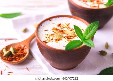 Traditional Indian almond lassi curd with cardamon, mint and saffron served in terracotta glasses. Kesariya. Keshariya. Kesar. Yogurt smoothie
