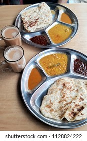 Traditional Indian breakfast with Roti Canai, Indian curries and milktea in Kuala Lumpur
