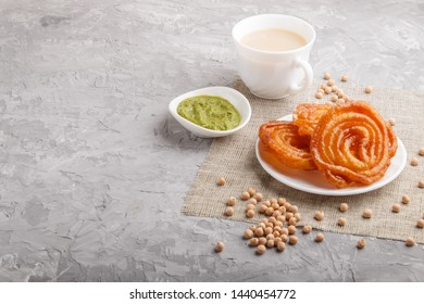 traditional indian candy jalebi in white plate with mint chutney on a gray concrete background. side view, copy space.