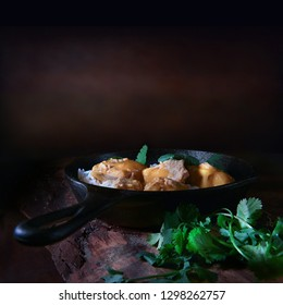 Traditional Indian cuisine, Chicken Curry with cilantro herb garnish and basmati rice shot against a rustic background with accommodation for copy space. The perfect image for your Indian menu cover