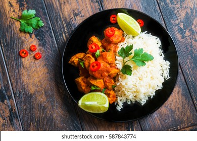 Traditional Indian cuisine, chicken curry with fresh chilli pepper, lime and parsley and boiled rice on a black ceramic plate on the wooden table, top view.