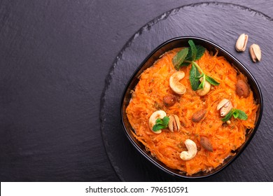 Traditional Indian cuisine. Homemade carrot Gajar halwa on black slate background. Copyspace, top view, flatlay