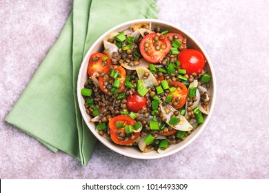 Traditional Indian cuisine. Lentil salad with green onion, cherry tomatoes, ginger and lime on gray slate background. Healthy food, vegetarian and vegan.  Copyspace, top view
