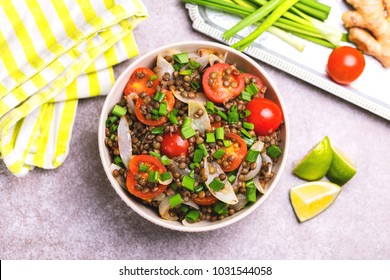 Traditional Indian cuisine. Lentil salad with onion, cherry tomatoes, ginger and lime on wooden background. Healthy food, vegetarian and vegan, clean eating, diet, detox.  Copyspace, horizontal view