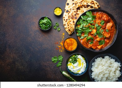 Traditional Indian dish Chicken tikka masala with space for text. Spicy curry meat in bowl, basmati rice, bread naan, yoghurt raita sauce on rustic dark background, top view, close up, copy space
