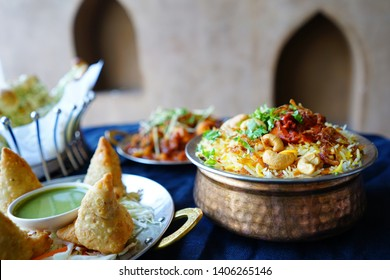 Traditional Indian dishes Chicken Biryani Rice and Samosas on dining table with tablecloth, blurred Aloo Gobi and Naan bread. Ramadan food preparation for iftar meal during the holy month / copy space