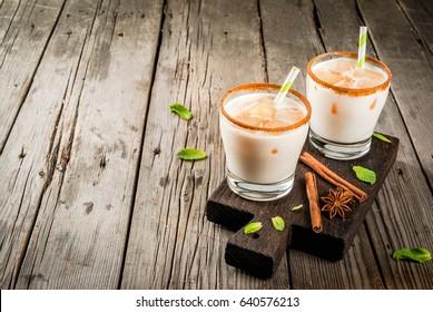 La boisson traditionnelle indienne est le thé glacé ou le chai masala, avec des glaçons de chai, du lait et des feuilles de menthe. Avec des pailles rayées, sur une planche en bois. Sur une vieille table en bois rustique. Espace de copie