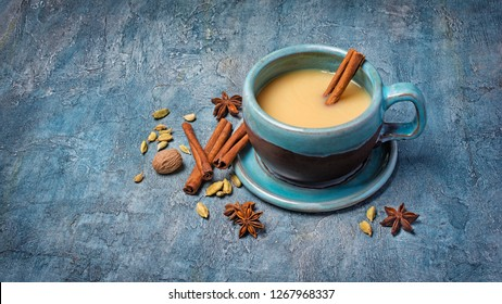 Traditional indian drink masala chai tea with milk and spices as cinnamon stick, green cardamom, anise star and nutmeg on blue concrete background