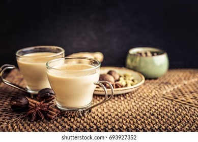 Traditional indian drink - masala chai tea (milk tea) with spices on rattan tray