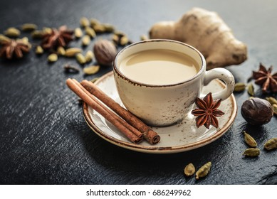 Traditional indian drink - masala tea with spices on black stone  background