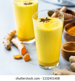 Traditional indian drink turmeric golden milk in a glass with ingredients, ginger, curcuma, honey on a kitchen table