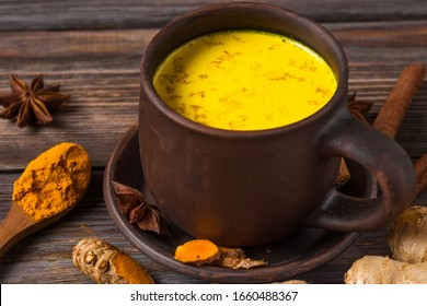 Traditional Indian drink turmeric latte or golden milk with cinnamon, ginger, anise, pepper and turmeric on rustic wooden table. Healthy drink
