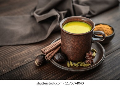 Traditional Indian drink turmeric milk is golden milk with cinnamon, cloves, pepper and turmeric on a wooden background with spices