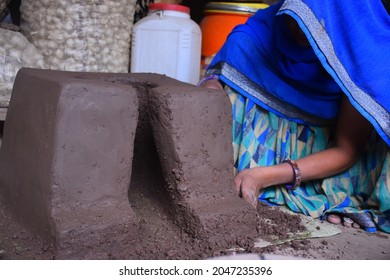 Traditional Indian earthen cooking stove Countryside clay stove, Indian rural woman making stove with clay, way of making food on open fire in old Indian kitchen