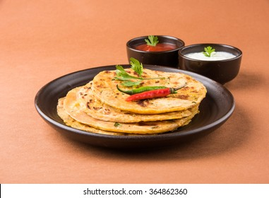 Traditional Indian food Aloo paratha or potato stuffed flat bread. served with tomato ketchup  and curd over colourful or wooden background. Selective focus