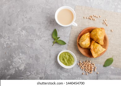 traditional indian food samosa in wooden  plate with mint chutney on a gray concrete background. top view, copy space, flat lay.