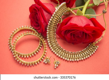Traditional Indian gold jewelry and red roses on bright background.