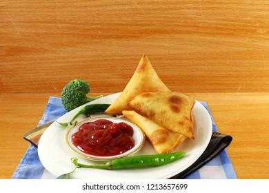 traditional indian gujarati food vegetable samosa with tomato sauce