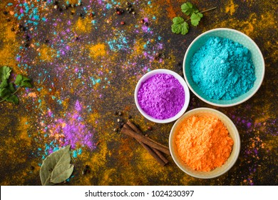 Traditional Indian Holi colours powder, spices, rustic background. Indian Holi holiday. Holi celebration. Top view. Festive Indian table setting. Space for text. Holi concept. Decoration with paints