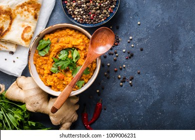 Traditional Indian lentils Dal, naan butter bread. Space for text. Indian Dhal spicy curry in bowl, spices, herbs, rustic concrete background. Top view. Indian food. Authentic Indian dish. Copy space