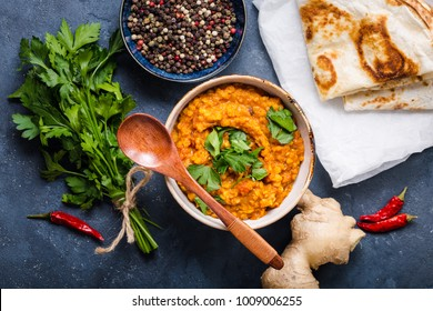 Traditional Indian lentils Dal, naan butter bread, fresh coriander. Indian Dhal spicy curry in bowl, spices, herbs, rustic concrete background. Top view. Indian food. Authentic Indian dish. Overhead